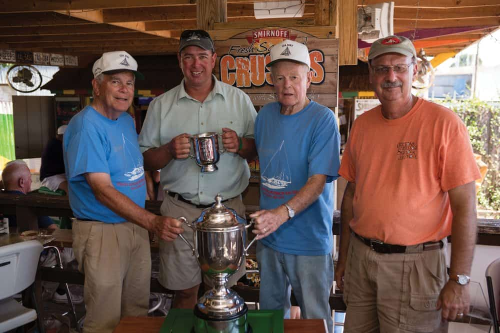 Ida May 's captain and owners receive their trophies from Race Chairman Lou Hindman (right).