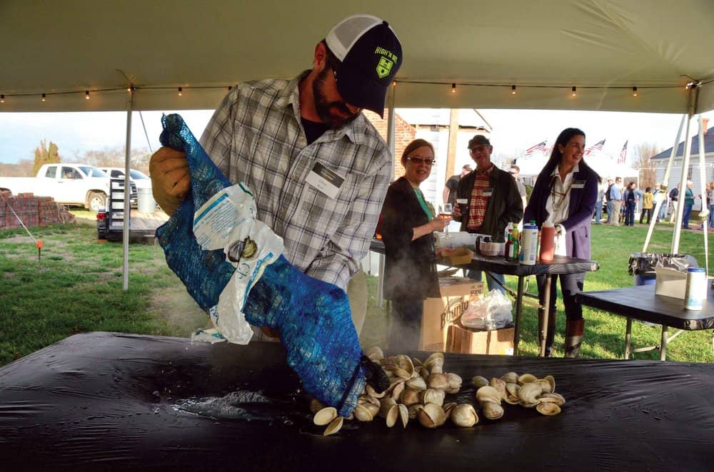 Chris Buck spreads freshly steamed Cherrystone clams on a table at the Barrier Islands Center Oyster Roast.