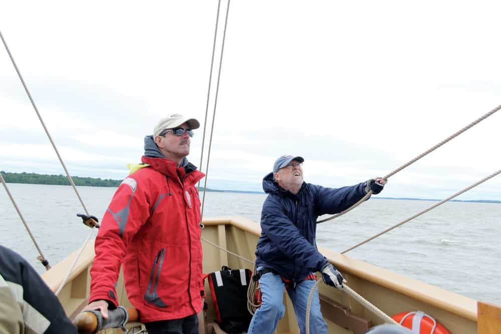 Captain Eric Speth (left) and volunteer Russ Sage (right) guide the 17th century replica vessel  Godspeed  along the James River.- photo Karen Soule