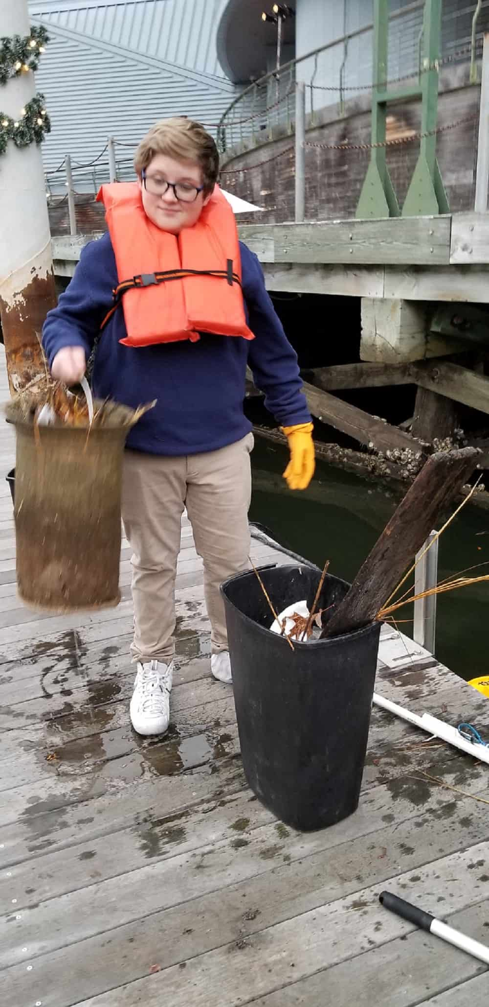 Nauticus Junior Scientists Club Alumni/Now Education Volunteer Dylan McNemar helps clean the Seabin. Photo: Nauticus.