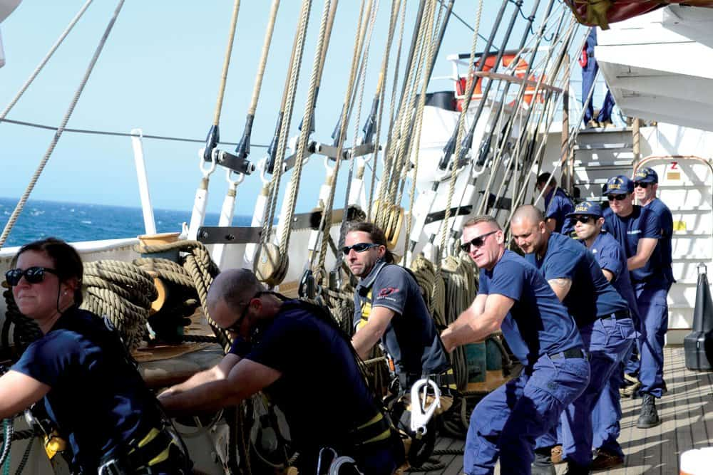 Justin Ailswoth (third from left) and Coast Guard crewmembers haul up one of the  Eagle 's 23 sails.Photo by Karen Soule.