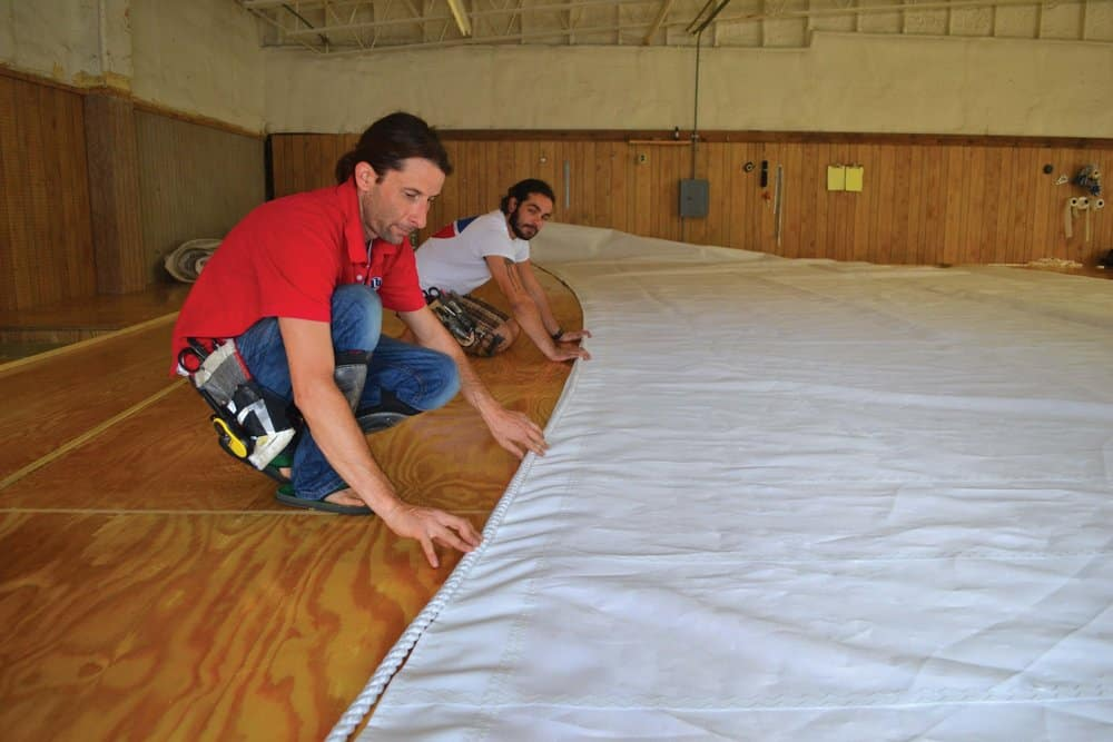 Sailmakers Ailsworth and Jake Pender lay out a sail's bolt-rope.Photo by Karen Soule.