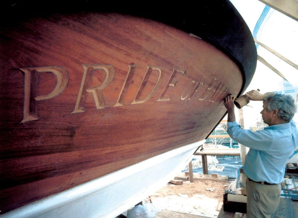 Hecklinger carving the name board on the original Pride.He also carved Pride of Baltimore II's. Photo by Fred Hecklinger.